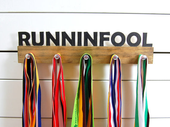 Our running medal holder is a great gift for the crazy runner in your life so they can display all of their awesome awards. This design comes in a variety of colors, or you can pick from our other choices of sports or phrases. Better yet, tell us your own personal mantra so we can customize a unique medal holder just for you!