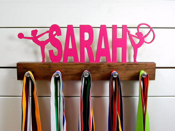 Our personalized rhythmic gymnastics medal holder is a unique gift for the gymnast in your life. This display will be the perfect way for her to show off all of her well-deserved awards. This design comes in a variety of colors, or you can pick from our other choices of sports or phrases so we can customize it just the way you want!