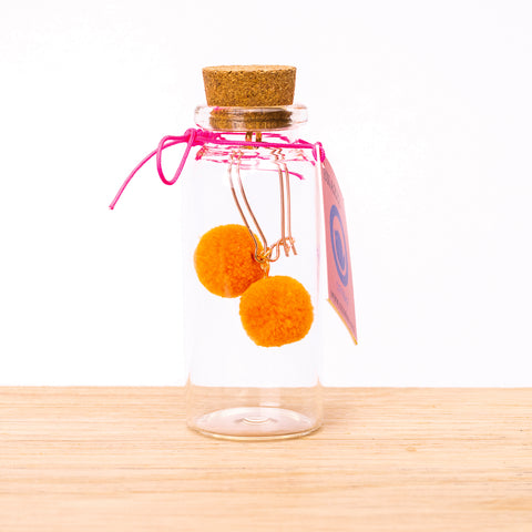 pom pom earrings in glass bottle