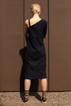 back view - model wears a-symmetric navy midi dress made from organic cotton with one hand embroidered strap reading CHOOSE HAPPINESS