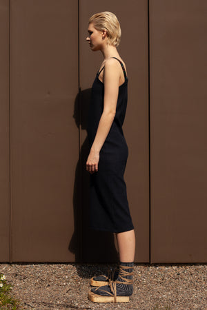 side view - model wears a-symmetric navy midi dress made from organic cotton with one hand embroidered strap reading CHOOSE HAPPINESS