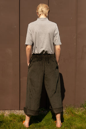 back view of model wearing sustainable clothing outfit - organic cotton and bamboo hand embroidered t-shirt with wide leg cropped organic cotton corduroy trousers