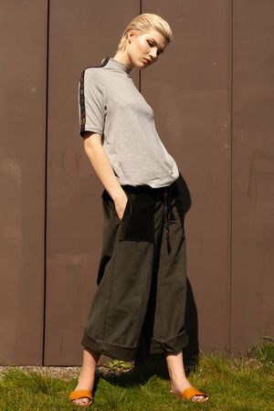 model wears sustainable light grey organic cotton and bamboo t-short with wide leg organic cotton corduroy trousers in dark green