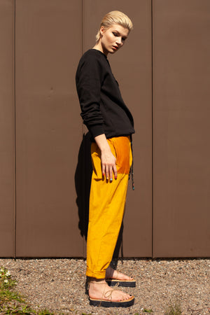 side view of model wearing tapered organic cotton mustard yellow corduroy trousers with hand embroidered tie waist reading CHOOSE HAPPINESS and black organic cotton sweatshirt