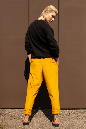 back view of model wearing tapered organic cotton mustard yellow corduroy trousers with hand embroidered tie waist reading CHOOSE HAPPINESS and black organic cotton sweatshirt