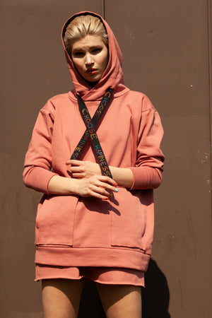 close up of model wearing salmon pink organic cotton oversized hoodie with hand embroidered black cord reading CHOOSE HAPPINESS