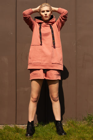 front view of model wearing salmon pink organic cotton mini skirt and matching oversized organic cotton hoodie