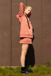 side view of model wearing salmon pink organic cotton mini skirt and matching oversized organic cotton hoodie