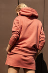 back view of model wearing salmon pink organic cotton mini skirt and matching oversized organic cotton hoodie