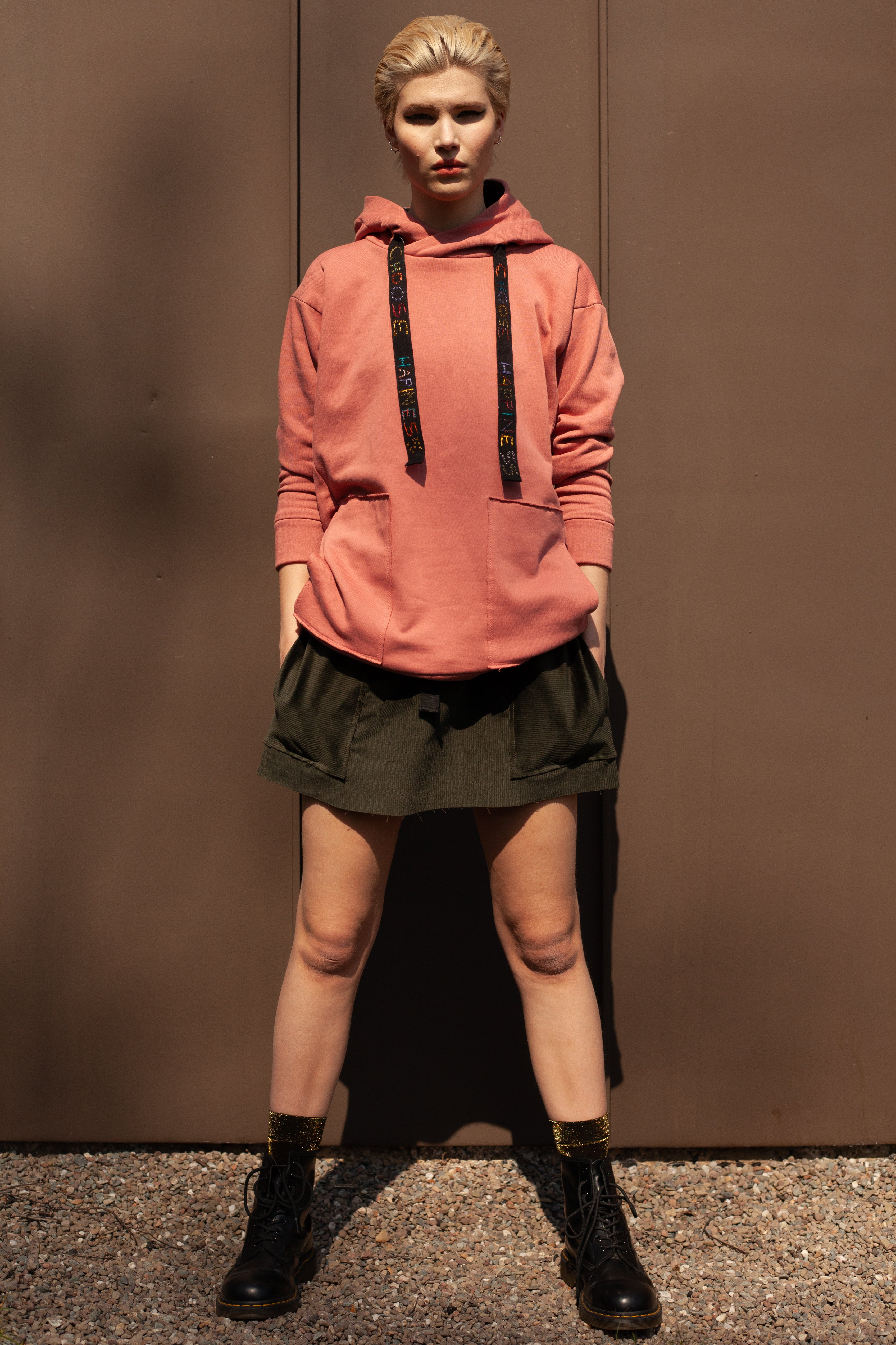 model wearing organic cotton corduroy mini skirt with oversized organic cotton salmon pink hoodie with hand embroidery
