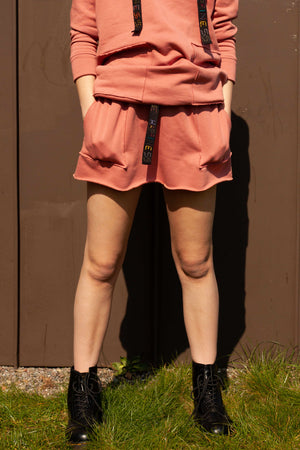 close up of model wearing salmon pink organic cotton mini skirt with hands in pockets