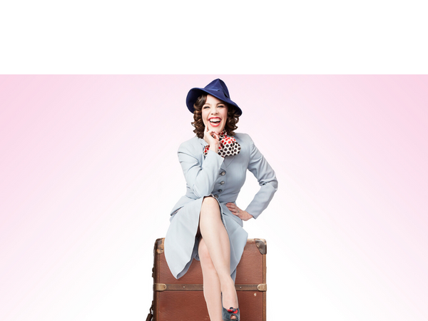 Allison Maldonado in a 40s outfit sitting on a vintage suitcase on a pink background