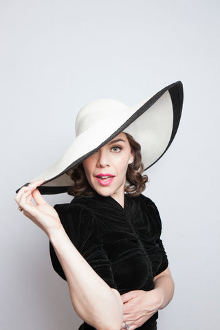 Allison Maldonado in a black dress with large white hat