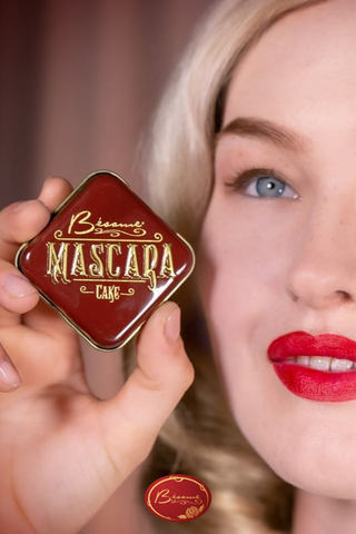 Woman wearing cruelty-free Bésame red lipstick holding a Cake Mascara container