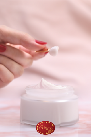 Hand taking a sample of Bésame's Cold Cream from a glass container