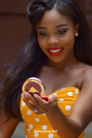Woman wearing a yellow polka dot dress and red lipstick holding a compact powder