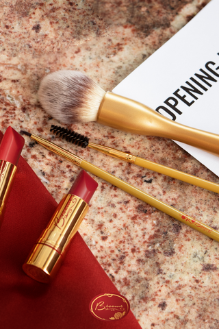 Bésame's red lipstick and lipstick and makeup brushes on marble surface