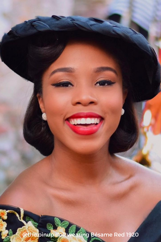Black woman smiling, wearing a black hat and Bésame's red lipstick