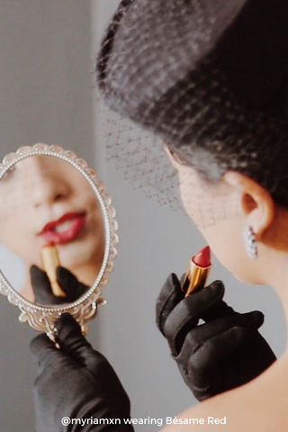 Woman wearing black gloves and black hat holding a mirror and applying Bésame's Red Lipstick