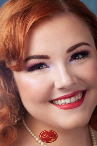 Red haired woman smiling wearing a perl necklace and Bésame's red lipstick