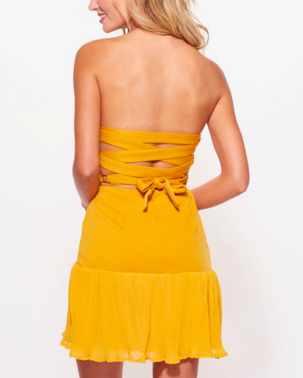 strapless bodycon mini dress with pleated chiffon trim and criss cross open back in mustard