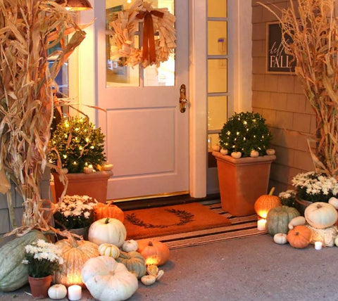 fall porch decor with pumpkins and tall corn stalks