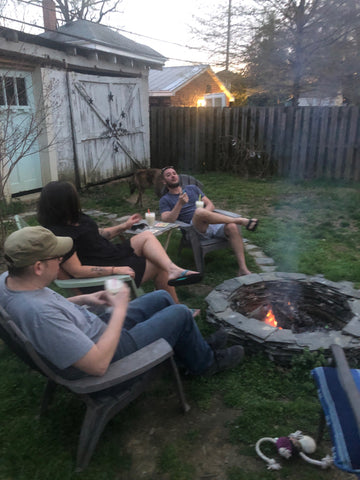 people having drinks arund a fire pit