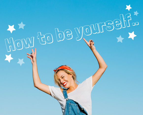 Woman with blonde hair and a red bandana hair tie, wearing a white tshirt and denim dungarees with one strap hanging down is smiling with her hands in the air, pointing to the lettering above her that says 'How to be yourself..' in white