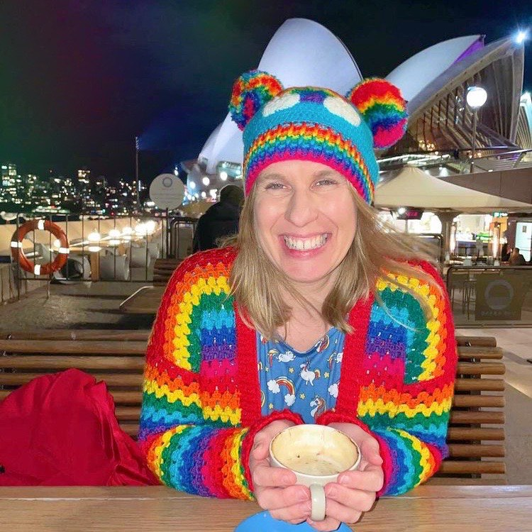 Helen, a white woman with shoulder length blonde hair is sitting on a bench at a table outside of a cafe. In the background there is a dark night sky and the Sydney Opera can be seen behind her. Helen is holding a cup of what seems to be coffee with both hands and has a wide smile on her face. Helen is wearing a blue dress with rainbow cloud print, a crocheted rainbow striped cardigan and a turquoise crocheted hat with rainbow pom pom 'ears', a rainbow cloud motif on the front and a rainbow striped ribbed brim.