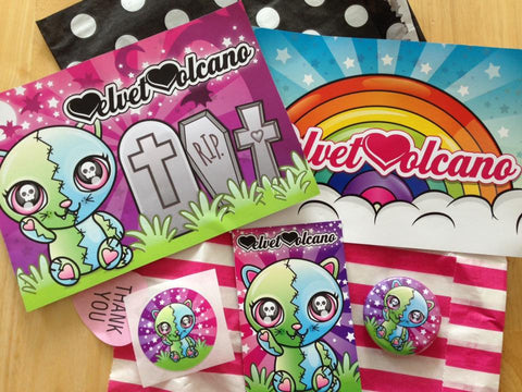 Photo shows 2 flyers, 2 small paper bags, a sticker, a button badge and a business card on a wooden backdrop. To the left of the image the first flyer features a cartoon cat inspired by Frankenksteins Monster in a graveyard with tombstones and bats, the sky is purple. The flyer to the right of this features a rainbow with clouds underneath it and a sunburst style turquoise background with stars. Above the flyers is a black paper bag with white polka dots, laying flat. Below the flyers is a bright pink and white striped paper bag, laying flat. On top of this bag is a round sticker featuring the FrankenKitty design, next to a business card with the same design and on the right of that is a FrankenKitty badge design.