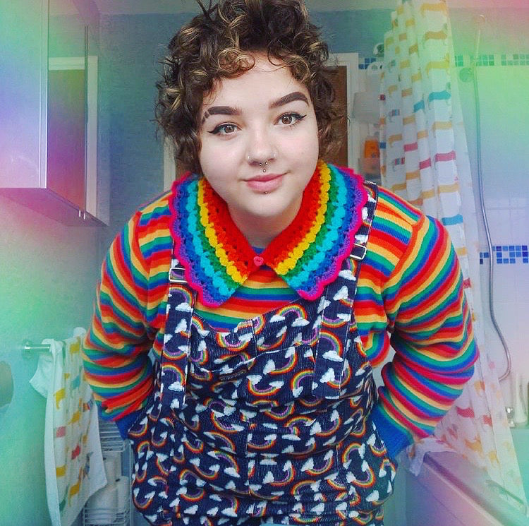 Samantha wearing a crocheted rainbow striped collar, rainbow striped long sleeve t-shirt and a pair of navy dungarees with a rainbow cloud print.