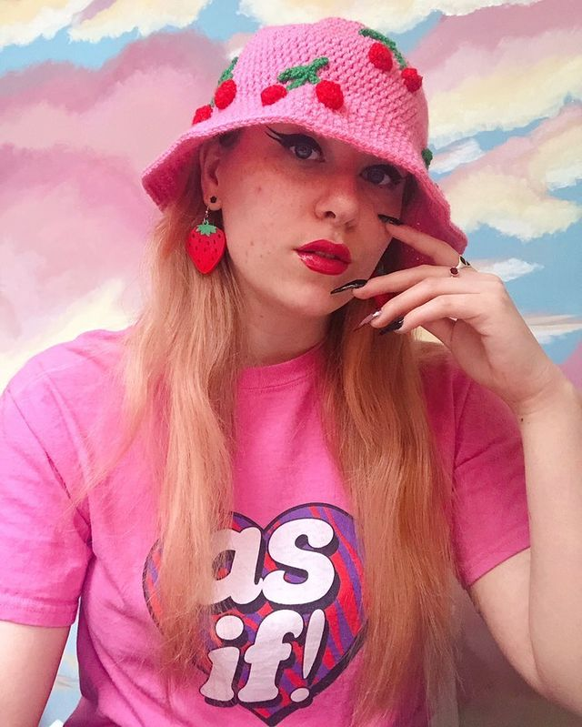 """Brooke is wearing a bubblegum pink crocheted bucket hat with red and green cherries on it, Brooke is also wearing a bright pink T-shirt that says """"as if!"""" in reference to the 90's cult film Clueless"""