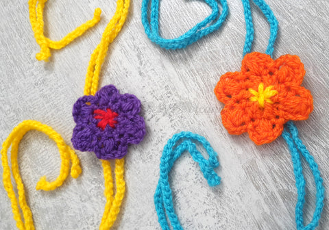 Crochet Flowers in Purple and Orange with braided strands in turquoise and yellow