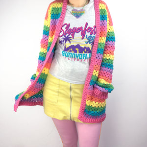 A woman wearing a VelvetVolcano Pastel Rainbow Striped Crochet Cardigan, a sparkly pastel rainbow heart necklace, a graphic tee, a pastel yellow mini-skirt and pastel pink leggings.