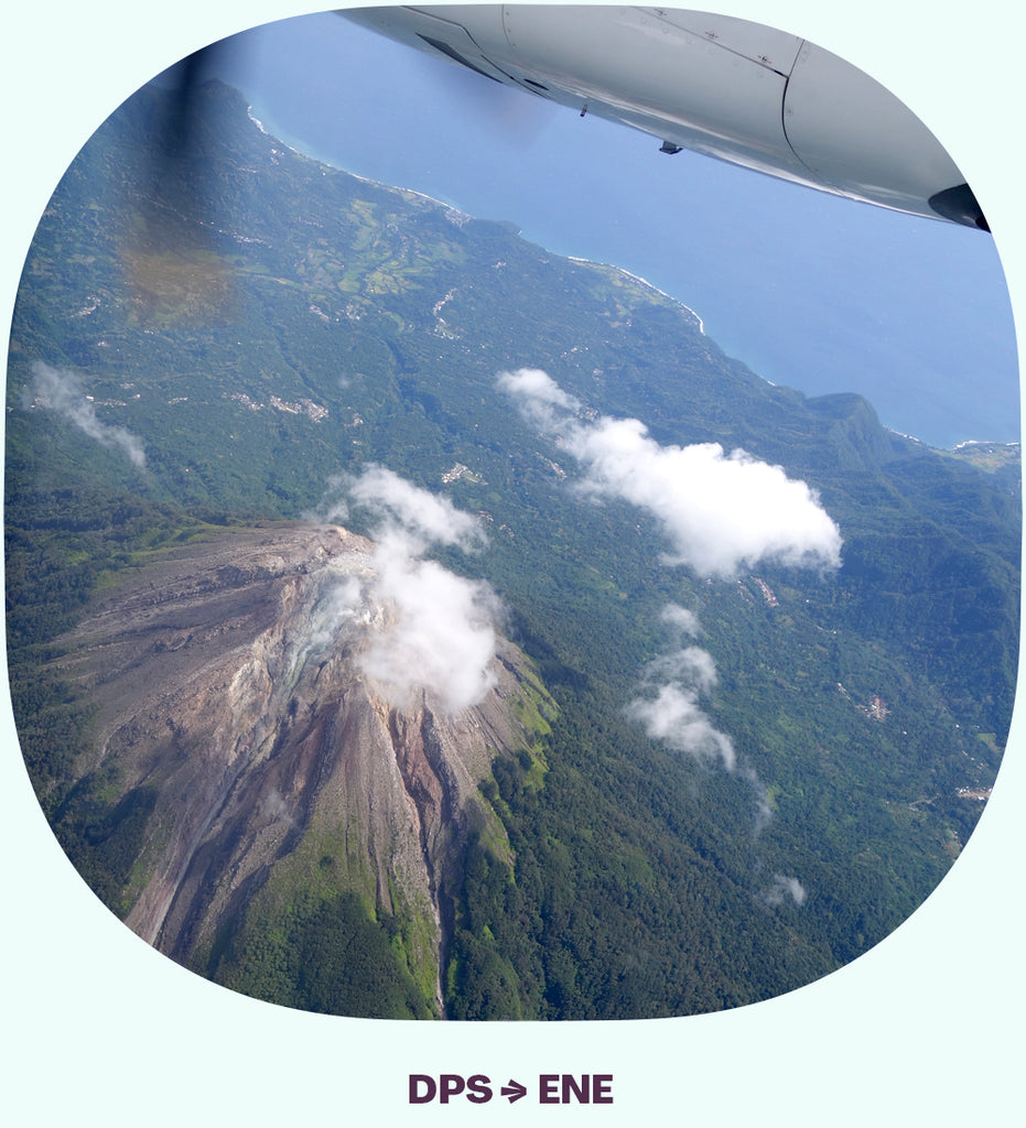 The propeller of an airplane and the view of a volcano below.