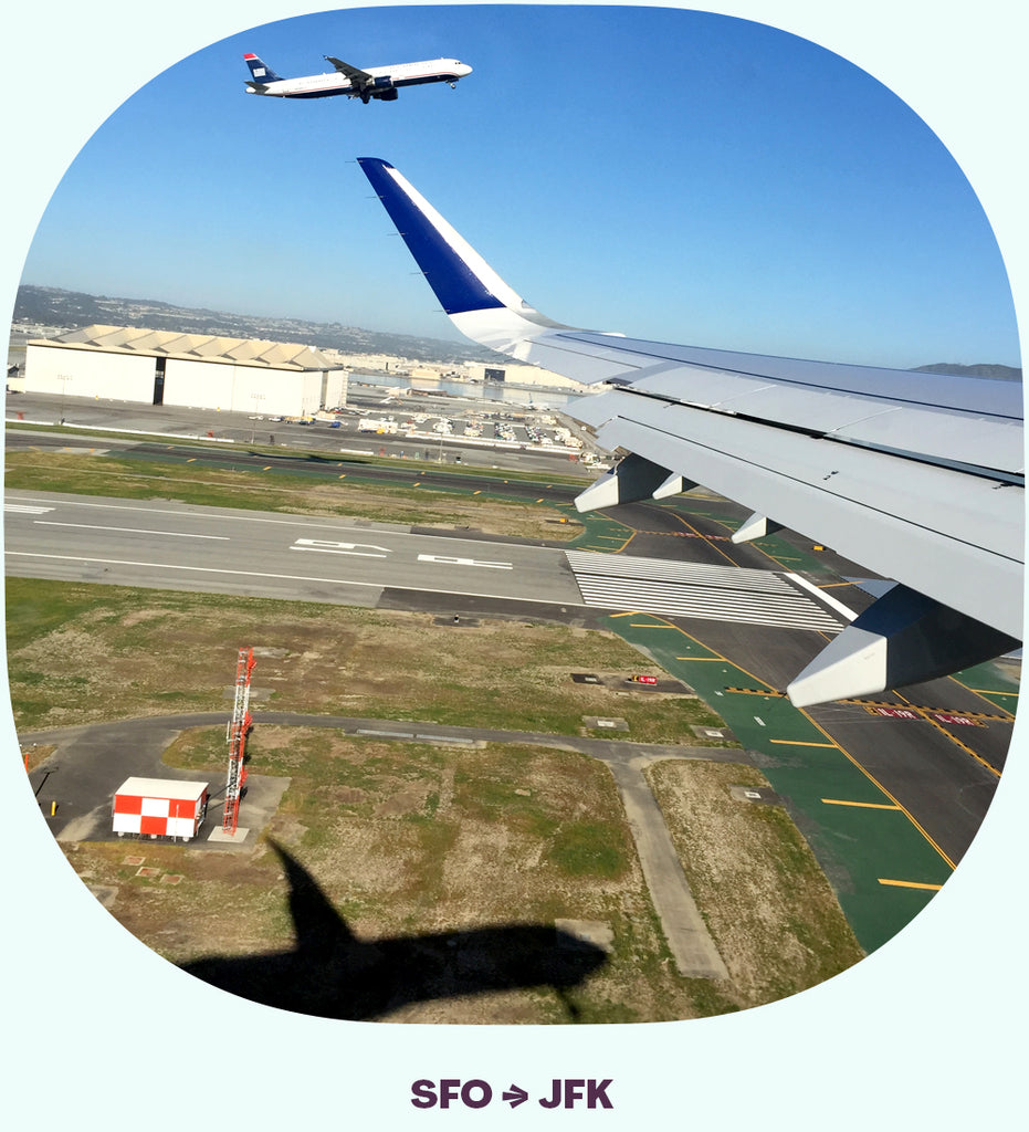The wing of an airplane just after takeoff, with another plane taking off on the next runway