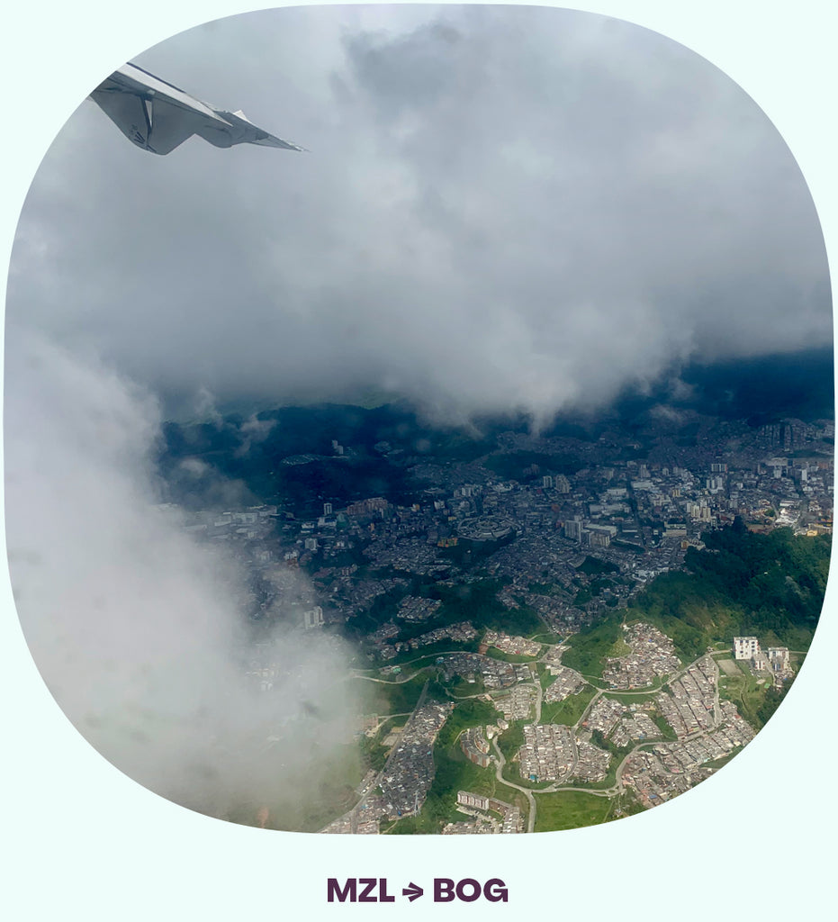 An airplane wing going into the clouds, with a peek of a town visible through the clouds.