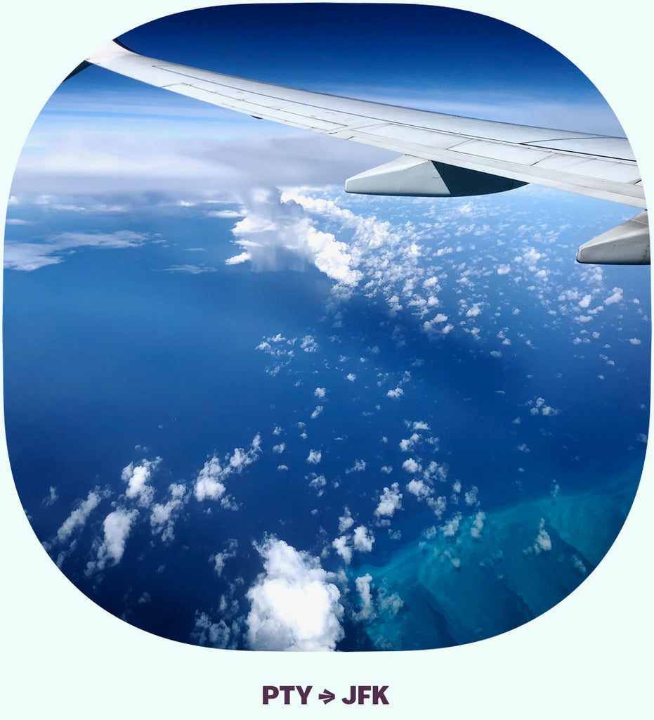 An airplane wing over an ocean, with a small raincloud below