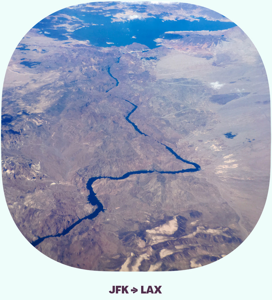 Looking down over the desert, with a river, dam, and a lake.