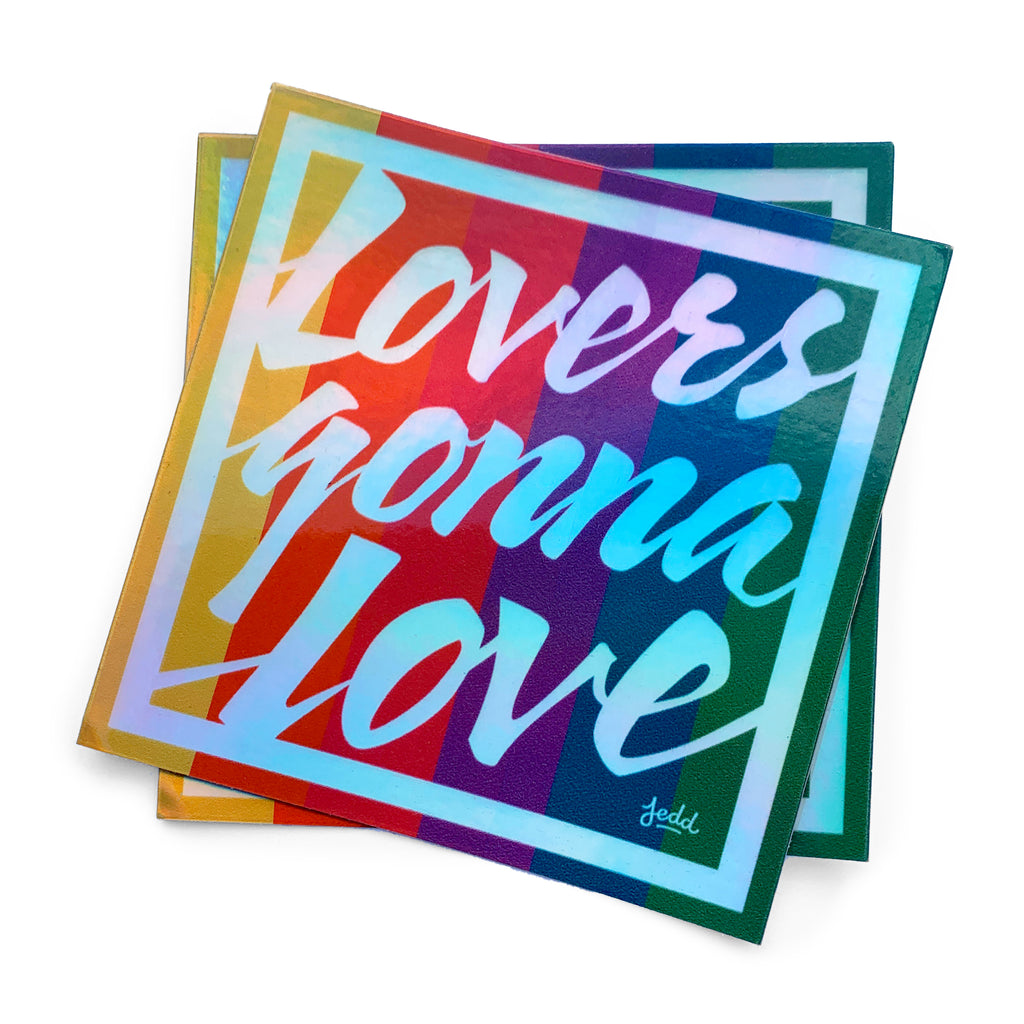 Two holographic stickers with a design that says Lovers Gonna Love