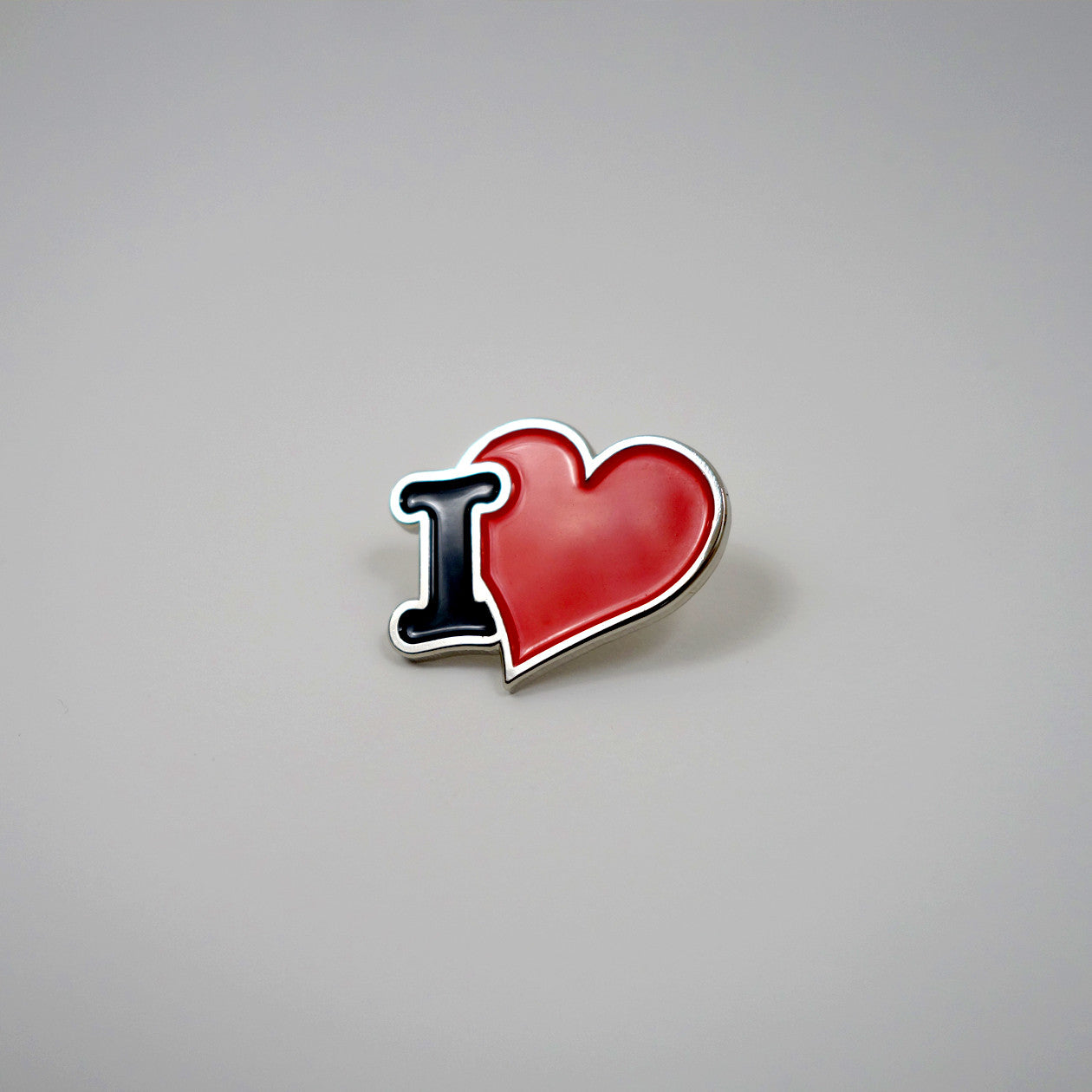 "A small enamel pin that that has a ""I Heart"" design."