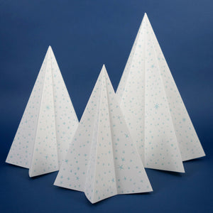 A set of three white letterpressed Christmas trees.