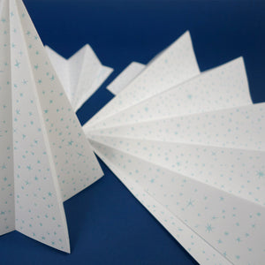 A set of three white letterpressed Christmas trees, with two shown unassembled.