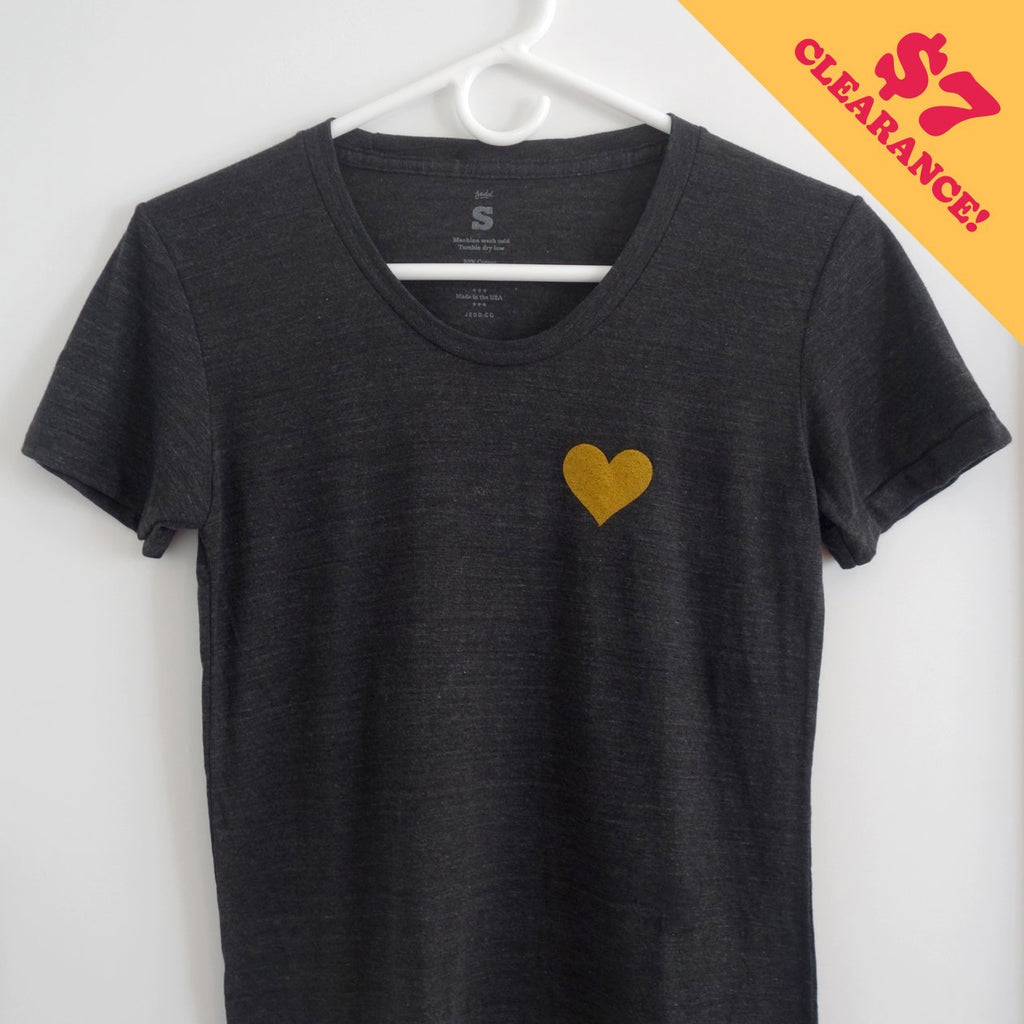 A gray t-shirt with a heart of gold printed on the upper chest.