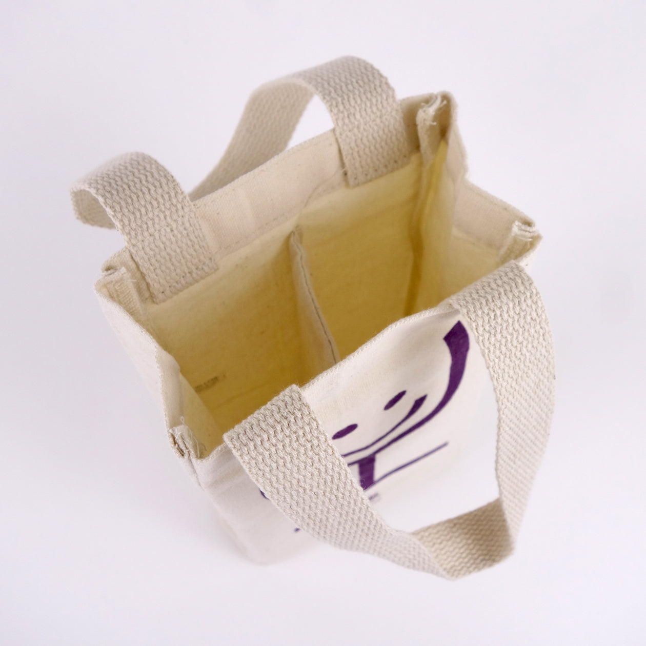 Interior detail of a canvas wine tote showing a center divider to hold two wine bottles.