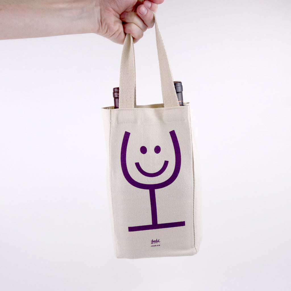 A canvas wine tote with a glass of wine smiley face illustration screen printed in purple.