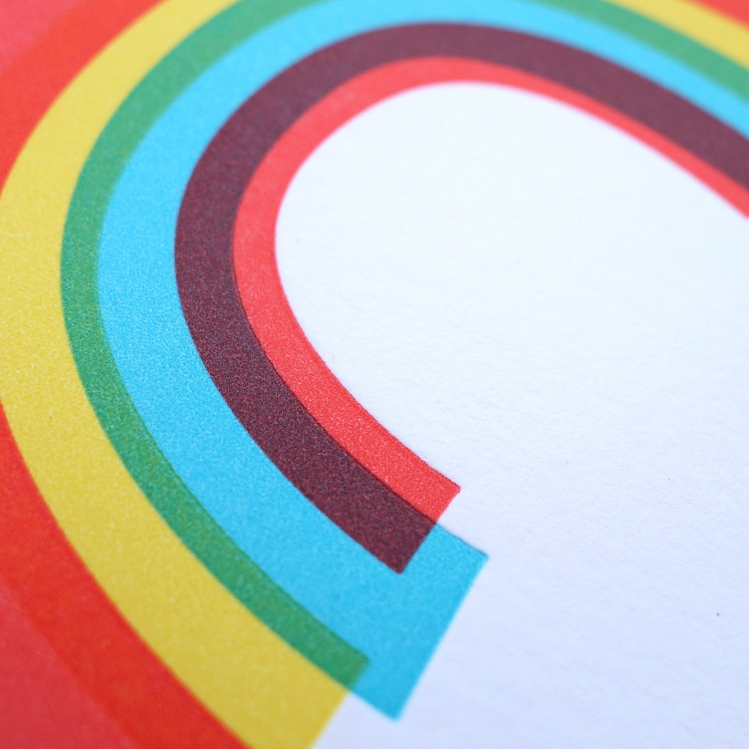 Detail of the letterpress texture of a white greeting card with a rainbow