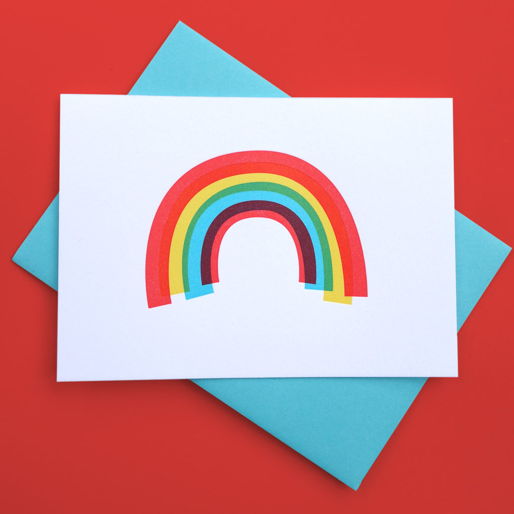 A white greeting card with a rainbow