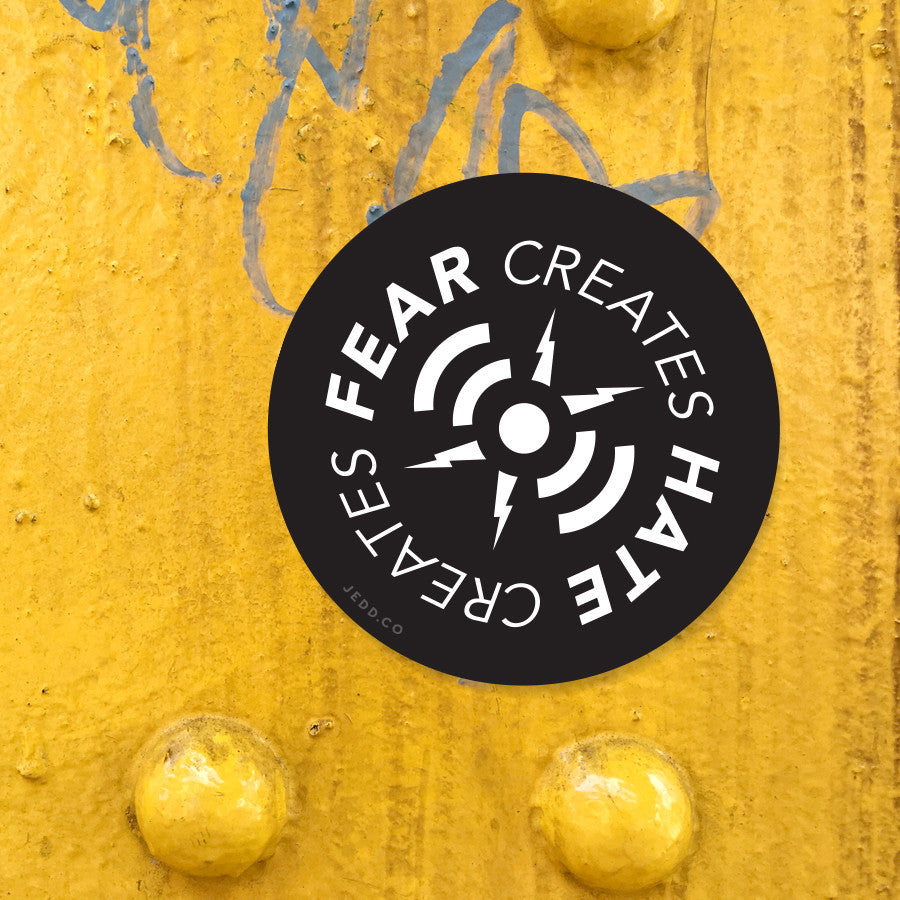 "A black sticker that reads in a continuing circle, ""Fear creates hate creates fear..."""
