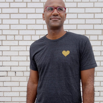 A cute man wearing a dark grey shirt with a heart of gold design